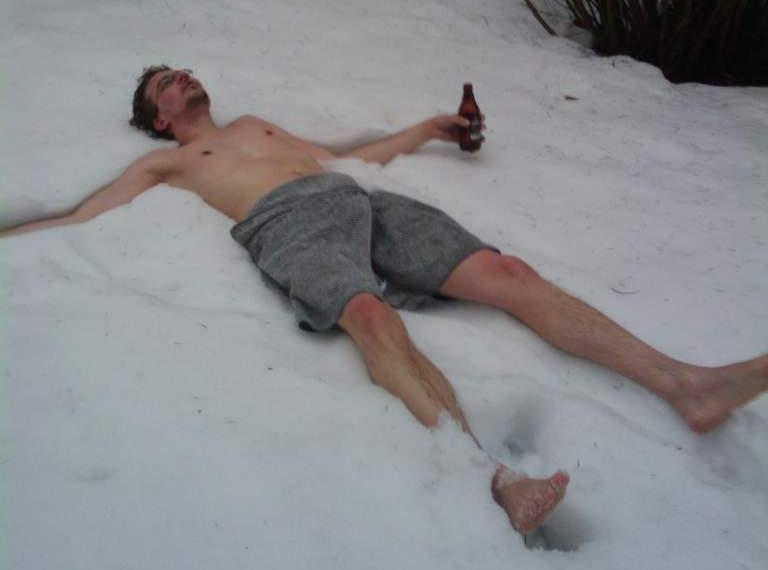 Image of amette lying in snow with only a towel and a beer